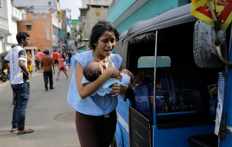 A Sri Lankan woman living near St. Anthony's shrine runs for safety with her infant after police found explosive devices in a parked vehicle in Colombo. Source: AP