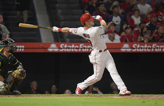 Los Angeles Angels' Taylor Ward, right, hits a two-run home run while Oakland Athletics catcher Jonathan Lucroy watches during the second inning of a baseball game Friday, Sept. 28, 2018, in Anaheim, Calif. (AP Photo/Mark J. Terrill)