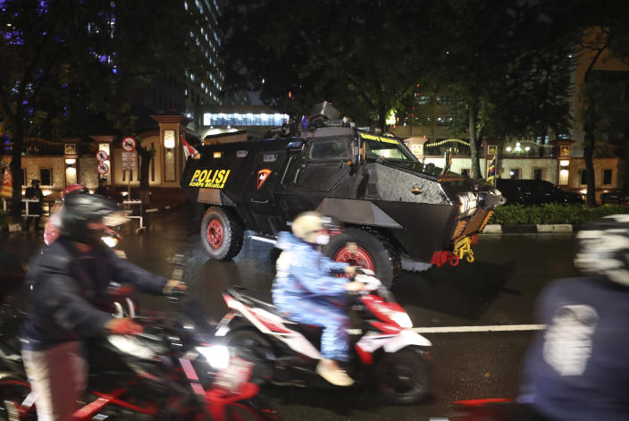 Motorists ride past a police armored vehicle parked outside the National Police Headquarters following a suspected militant attack in Jakarta, Indonesia, Wednesday, March 31, 2021. A woman entered the Indonesian National Police Headquarters in Jakarta and pointed a gun at several officers before being shot dead by police, in the latest in a series of militant attacks in the world's most populous Muslim nation. (AP Photo/Dita Alangkara)