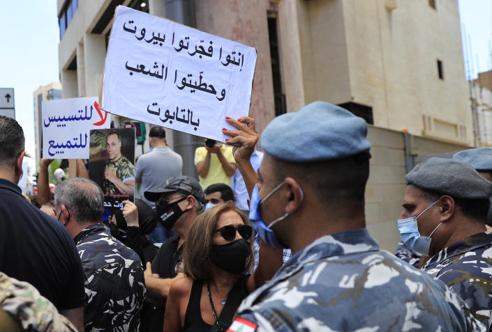 """A woman who lost her relative during the last year's massive blast at Beirut's seaport, holds an Arabic placard that reads:""""You exploded Beirut and you put the people in the coffin,"""" during a protest near the tightly-secured residents of parliament speaker Nabih Berri, in Beirut, Lebanon, Friday, July 9, 2021. The protest came after last week's decision by the judge to pursue senior politicians and former and current security chiefs in the case, and requested permission for their prosecution. (AP Photo/Hussein Malla)"""