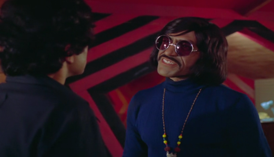 Turtlenecks, bell-bottoms, platform shoes, round rose tinted glasses, and a ridiculous pre-Anton Chigurh haircut round off Puri's most eclectic look.