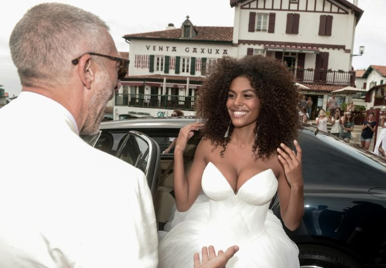 French actor Vincent Cassel greets his bride-to-be model Tina Kunakey as she arrives for their wedding ceremony at the town hall in Bidart in southwest France