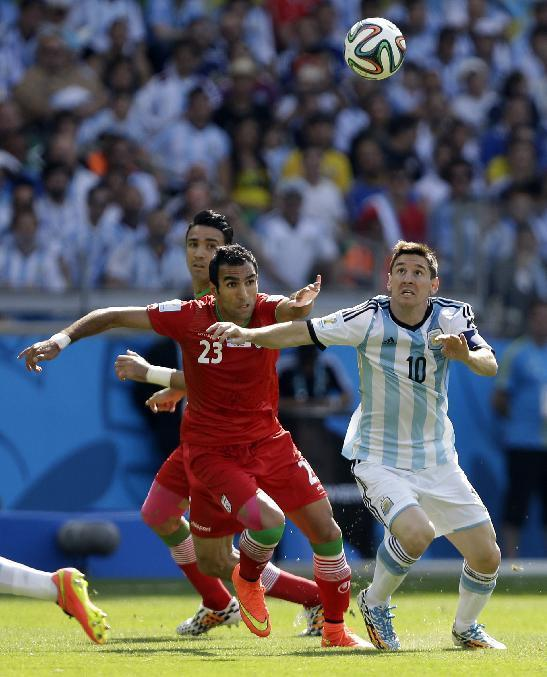 Argentina's Lionel Messi keeps his eyes on the ball while being chased by Iran's Mehrdad Pooladi during the group F World Cup soccer match between Argentina and Iran at the Mineirao Stadium in Belo Horizonte, Brazil, Saturday, June 21, 2014. (AP Photo/Fernando Vergara)