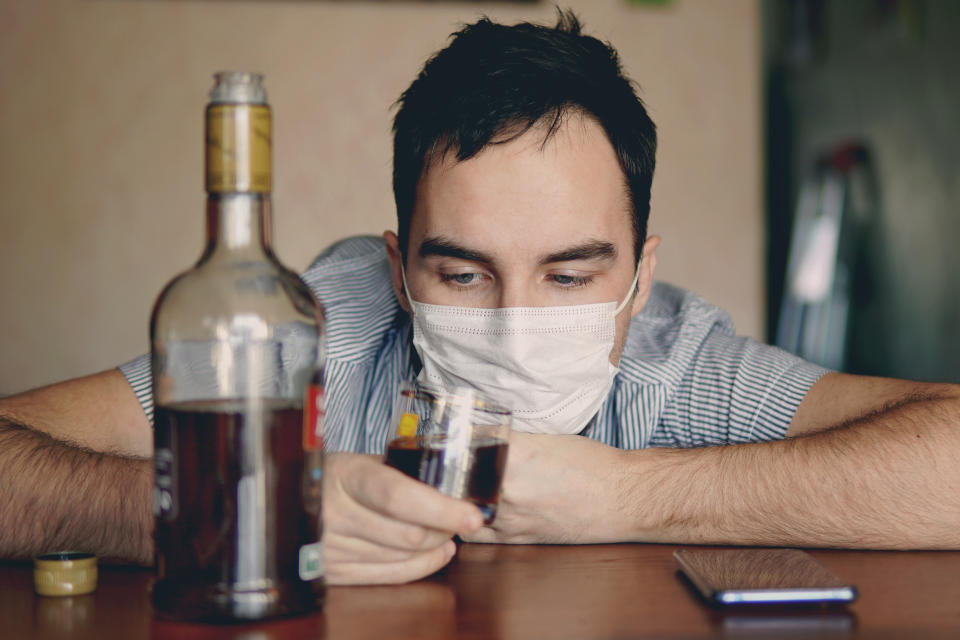 alcoholism, alcohol addiction and people concept - male alcoholic with bottle of rum at home. An unemployed specialist who got drunk alone out of boredom is quarantined in self-isolation.