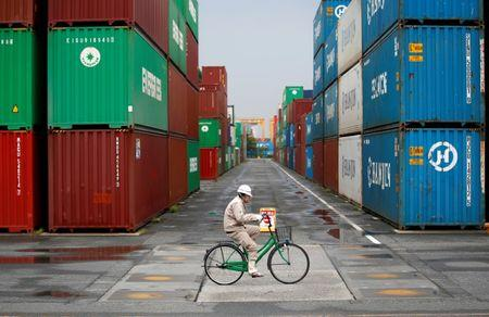 FILE PHOTO: A worker rides a bicycle in a container area at a port in Tokyo