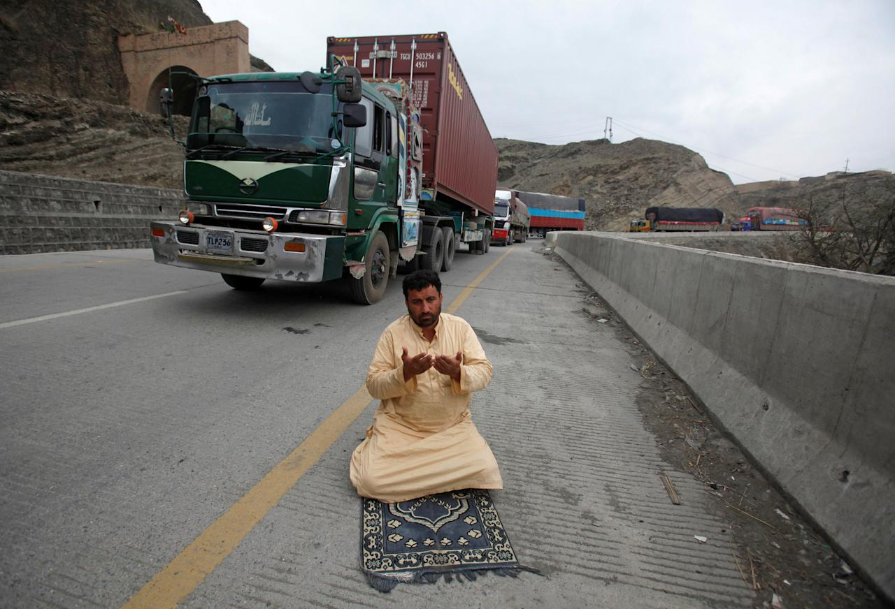 A truck driver offers afternoon prayers near his supply truck, after the opening of Pakistan Afghan Torkham border, in Landi Kotal, Pakistan March 21, 2017. REUTERS/Fayaz Aziz