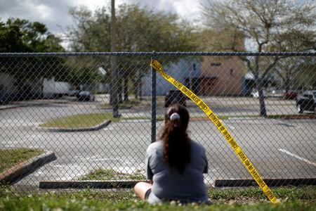 A woman mourns in front of the fence of the Marjory Stoneman Douglas High School, following a mass shooting in Parkland