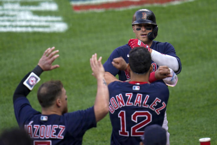 Boston Red Sox's Enrique Hernandez, top, is greeted near the dugout after hitting a solo home run off Baltimore Orioles starting pitcher Tyler Wells during the eighth inning of a baseball game, Thursday, April 8, 2021, on Opening Day in Baltimore. The Red Sox won 7-3. (AP Photo/Julio Cortez)