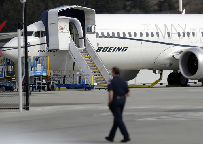 """FILE- In this March 14, 2019, file photo a worker walks next to a Boeing 737 MAX 8 airplane parked at Boeing Field in Seattle. U.S. prosecutors are looking into the development of Boeing's 737 Max jets, a person briefed on the matter revealed Monday, the same day French aviation investigators concluded there were """"clear similarities"""" in the crash of an Ethiopian Airlines Max 8 last week and a Lion Air jet in October. (AP Photo/Ted S. Warren, File)"""