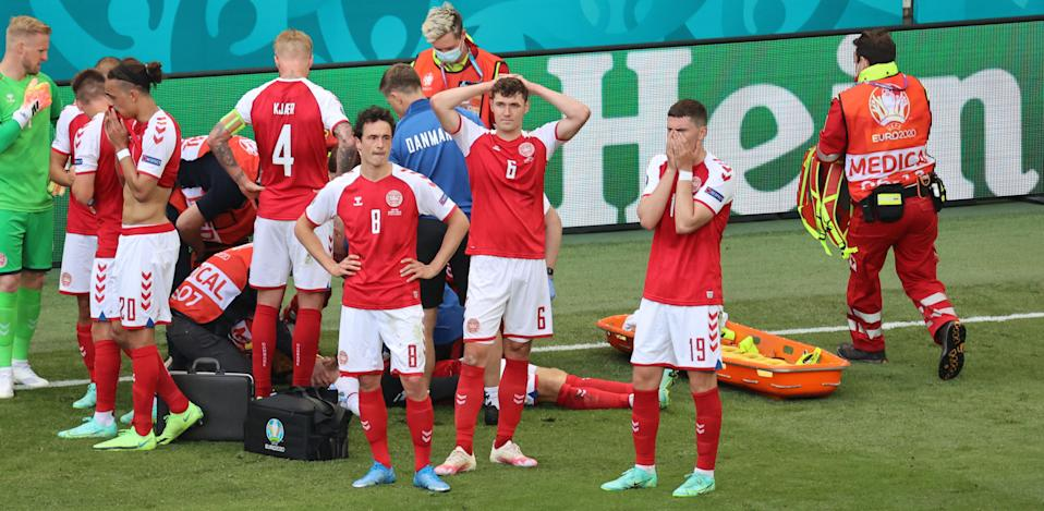 Denmark players react as paramedics attend to midfielder Christian Eriksen after he collapsed on the pitch during the during Saturday's Euro 2020 match against Finland. (Photo by Wolfgang Rattay/AFP via Getty Images)