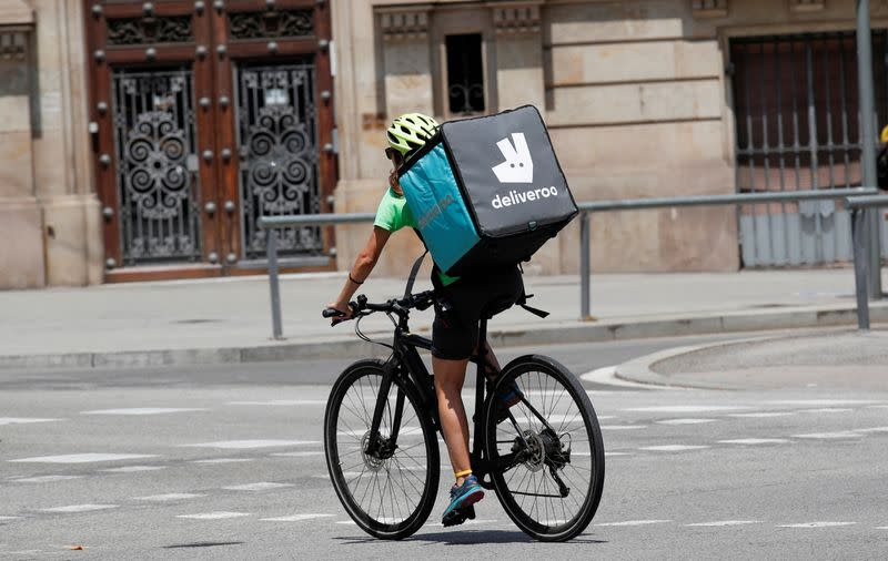 FILE PHOTO: A biker wearing a Deliveroo backpack drives in the central Barcelona