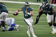 Philadelphia Eagles' Jalen Hurts (2) scrambles out of the pocket before throwing a pass with protection from offensive tackle Jordan Mailata in the first half of an NFL football game against the Dallas Cowboys in Arlington, Texas, Sunday, Dec. 27. 2020. (AP Photo/Michael Ainsworth)