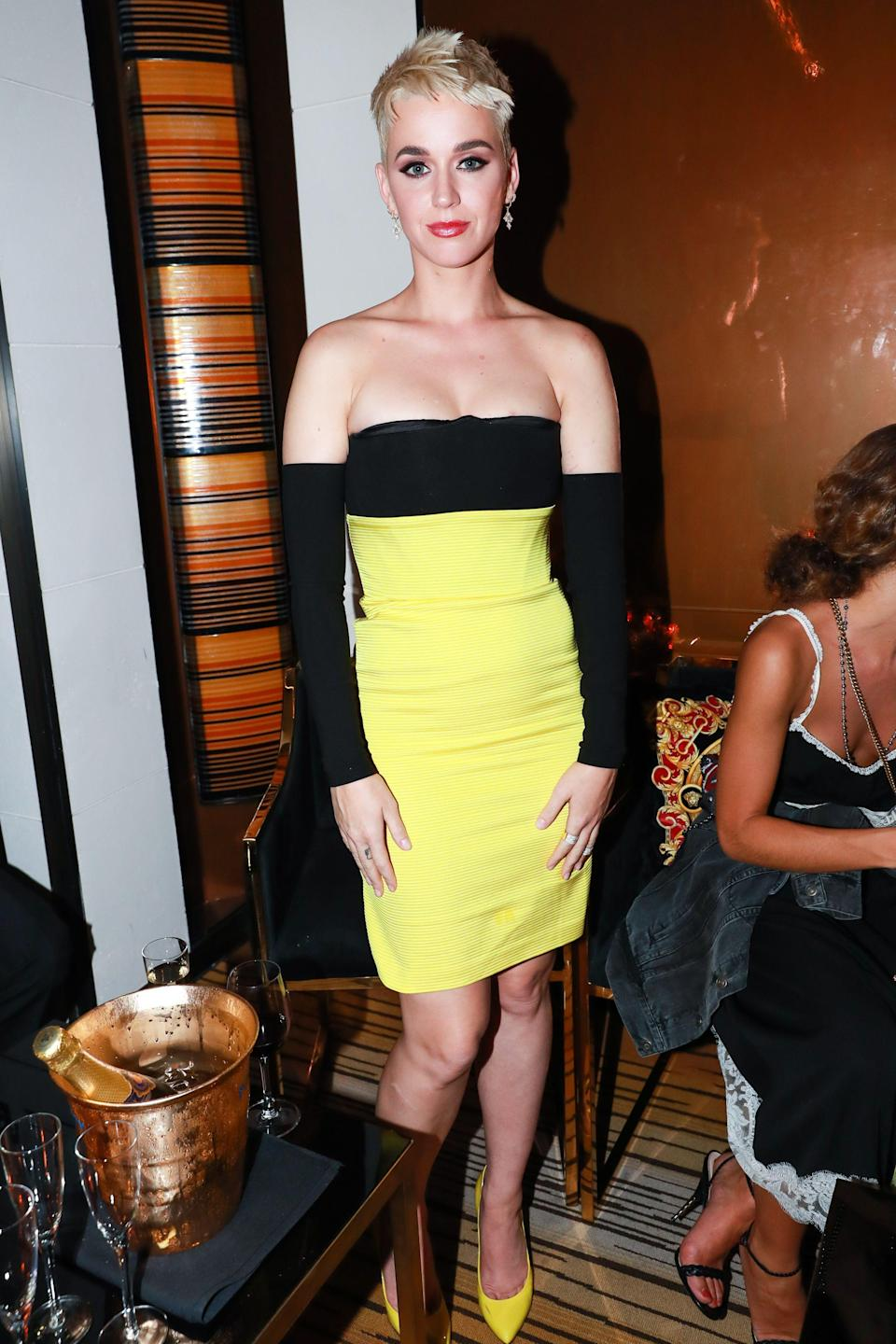 <p>The singer slipped off her wings and put on a yellow and black mini dress with matching stilletos. (Photo: Shutterstock) </p>