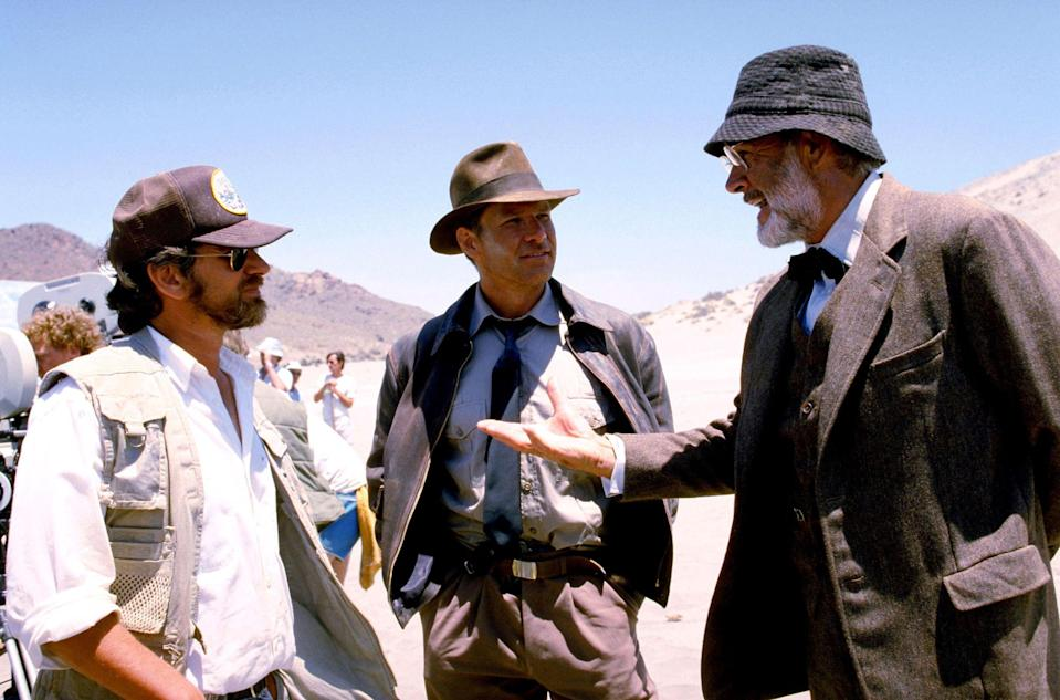"""<p>Indiana Jones is an institution. The hat. The grin. The John Williams score. The movies are a spectacle—packed with adventure, humor, and some questionable ancient history. Forty years ago, on June 12, 1981, Indy hit theaters for the first time in <em>Raiders of the Lost Ark</em>. If the boulder chase in the opening sequence didn't get you, Indy's fear of snakes sure did. (He was also the <a href=""""https://www.esquire.com/style/mens-fashion/a25848350/indiana-jones-style-fashion-outfits/"""" rel=""""nofollow noopener"""" target=""""_blank"""" data-ylk=""""slk:most stylish archaeologist"""" class=""""link rapid-noclick-resp"""">most stylish archaeologist</a> to appear on the silver screen.) To mark the anniversary, here are 25 rarely-seen behind-the-scenes photos from all four of the movies. And in case you didn't know, there's another movie on the way (read all about it <a href=""""https://www.esquire.com/entertainment/movies/a36684645/indiana-jones-5-release-date-cast-plot-explained/"""" rel=""""nofollow noopener"""" target=""""_blank"""" data-ylk=""""slk:here"""" class=""""link rapid-noclick-resp"""">here</a>). </p>"""