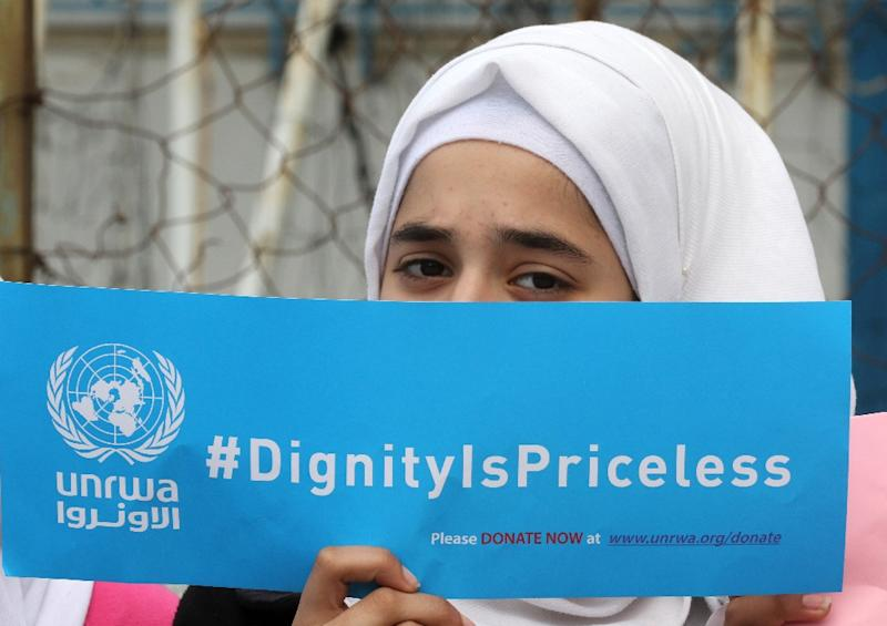 A Palestinian refugee holds a placard at a school belonging to the United Nations Relief and Works Agency for Palestinian Refugees (UNRWA) in the town of Sebline in Lebanon, on March 12, 2018, during a protest against US aid cuts to the organisation