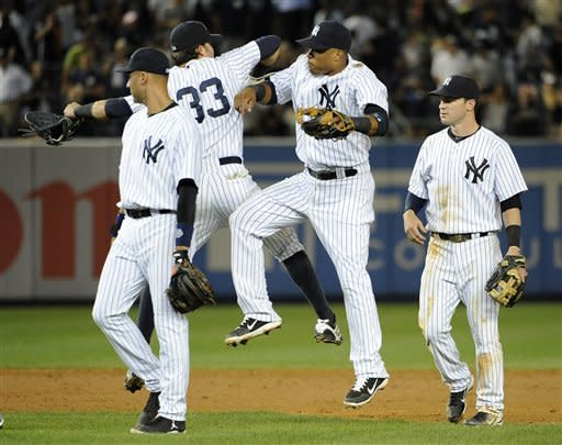 New York Yankees' Derek Jeter, Nick Swisher (33), Robinson Cano and Jayson Nix, right, celebrate their 2-1 win over the Toronto Blue Jays after the ninth inning of a baseball game on Tuesday, Aug. 28, 2012, at Yankee Stadium in New York. (AP Photo/Kathy Kmonicek)
