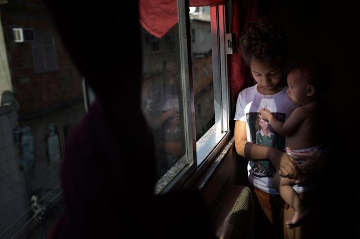 <p>Nayane stands next to the window of her room in the shantytown Parque Uniao in Rio de Janeiro, Brazil. in August 2016. She wears the picture of Ana Sophia's father on her t-shirt. She can't contain her tears when she remembers the fatal day in which her first born was left fatherless. (Photo: Rafael Fabrés) </p>