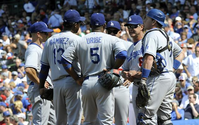 Los Angeles Dodgers manager Don Mattingly, second from right, talks to his team during a pitching change in a baseball game against the Chicago Cubs, Sunday, Aug. 4, 2013, in Chicago. (AP Photo/Joe Raymond)