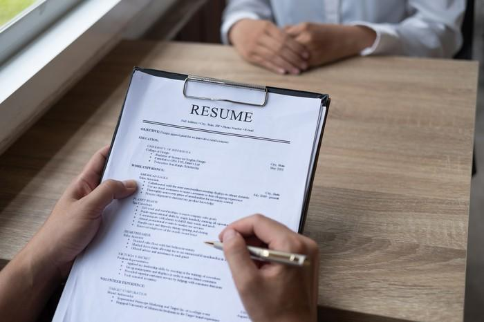Person holding a pen to a resume on a clipboard while sitting in front of an interviewee.