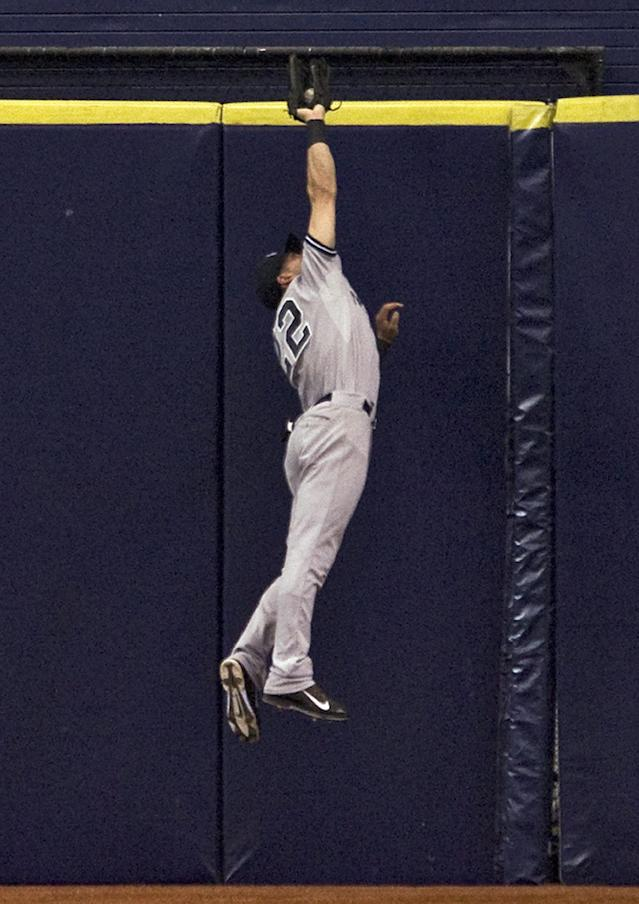 New York Yankees center fielder Jacoby Ellsbury robs Tampa Bay Rays' Ben Zobrist of an extra-base hit during the fourth inning of a baseball game Friday, April 18, 2014, in St. Petersburg, Fla. (AP Photo/Steve Nesius)
