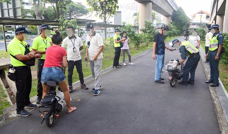 The LTA's active mobility enforcement officers, together with partners from NParks and volunteers, conducting checks on PMD users in Yishun on 17 July, 2019. (PHOTO: Land Transport Authority – We Keep Your World Moving/Facebook)