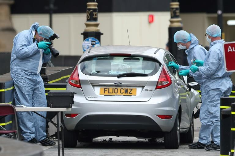 Police forensics officers work around a silver Ford Fiesta car that was driven into a barrier at the Houses of Parliament in London