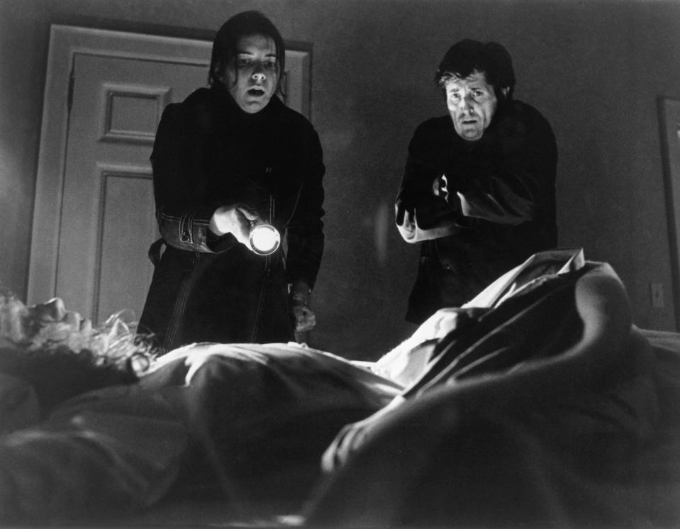 "(Original Caption) 1973- Kitty Winn holds a flashlight at Linda Blair, in bed, as Jason Miller watches in this scene from ""The Exorcist."""