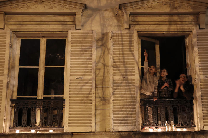 """A woman and her children applaud after they set up candles on their balcony in Versailles, Wednesday, March 25, 2020. France's bishops called for Catholics and non-Catholics alike to take part in Wednesday's candle-lighting, in a shared """"prayer for the dead, the sick and their loved ones, for all the medical personnel and all those who make the life of our country possible."""" The new coronavirus causes mild or moderate symptoms for most people, but for some, especially older adults and people with existing health problems, it can cause more severe illness or death. (AP Photo/Christophe Ena)"""