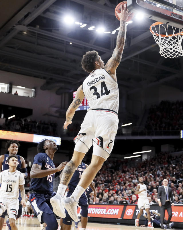 Cincinnati's Jarron Cumberland (34) shoots as Connecticut's Sidney Wilson (15) looks on in the first half of an NCAA college basketball game, Saturday, Jan. 12, 2019, in Cincinnati. (AP Photo/John Minchillo)