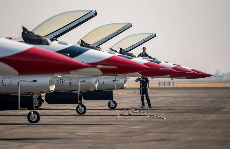 """Melvin Laxamana, top, and Charles Bolles, staff sergeants and crew chiefs with the U.S. Air Force Air Demonstration Squadron """"Thunderbirds,"""" prepare F-16 Fighting Falcons for flight at the start of the California Capital Airshow on Friday, Sept. 24, 2021, at Mather Airport in Sacramento."""