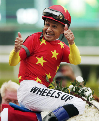 FILE - In this June 9, 2018, file photo, Jockey Mike Smith reacts after guiding Justify to win the Belmont Stakes horse race and the Triple Crown in Elmont, N.Y. The winning formula for a big race generally combines the talent of the horse, the prowess of the trainer and the skill of the jockey. Smith is now riding favored Improbable with familiar trainer Bob Baffert in Saturday's Preakness, bumping Irad Ortiz to new shooter Bourbon War.(AP Photo/Andres Kudacki, File)