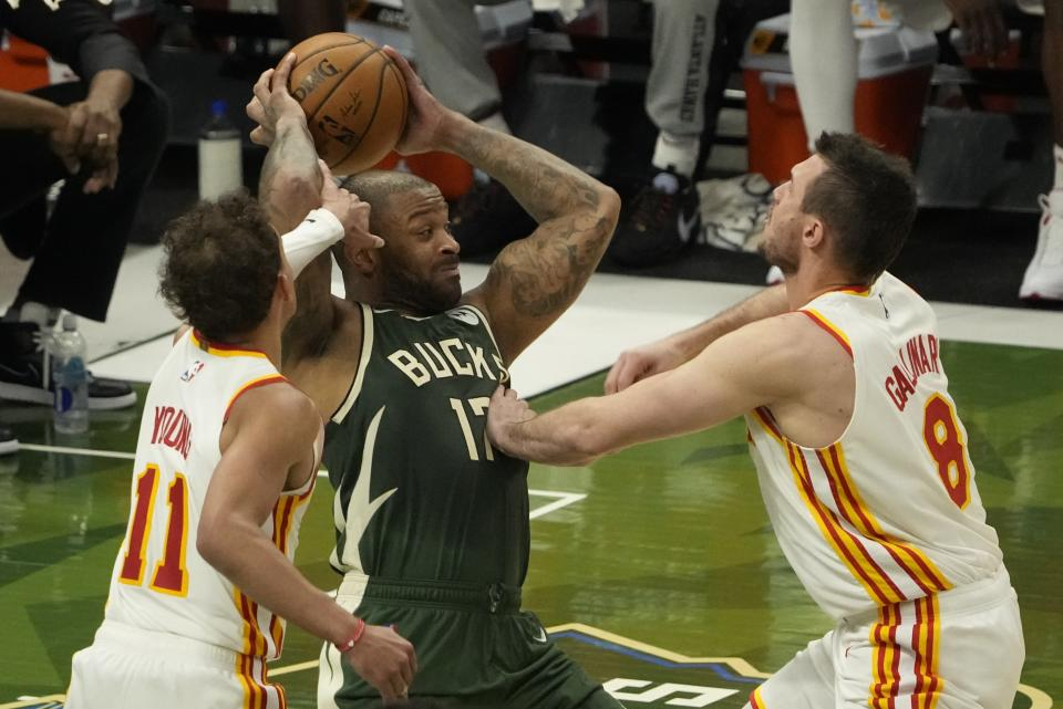 Atlanta Hawks' Onyeka Okongwu is defended by Atlanta Hawks' Trae Young and Danilo Gallinari during the second half of Game 1 of the NBA Eastern Conference basketball finals game Wednesday, June 23, 2021, in Milwaukee. (AP Photo/Morry Gash)