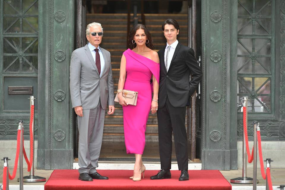 Catherine Zeta-Jones stuns in a hot pink number next to her husband Michael Douglas and son Dylan in Swansea. [Picture: Getty Images]