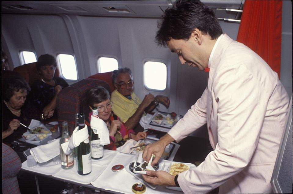 <p>A German flight attendant serving caviar to guests in 1990. Throughout the '80s and into the '90s, more men started to become flight attendants. </p>