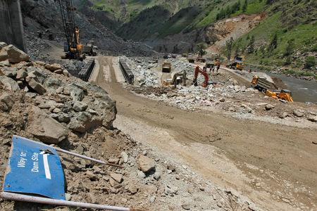 FILE PHOTO: Work is being done beside a signboard lying at the dam site of Kishanganga power project in Gurez, 160 km (99 miles) north of Srinagar June 21, 2012. REUTERS/Fayaz Kabli/File Photo