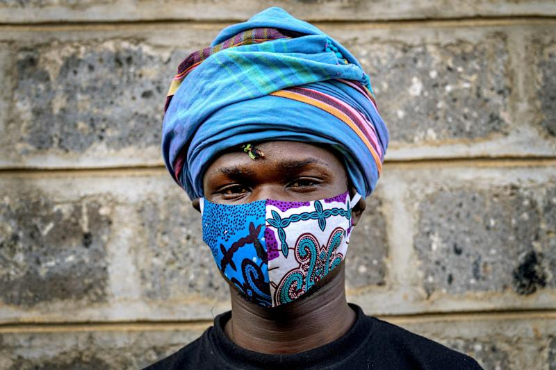 KENYA: Fashion designer David Avido, 24, poses for a portrait at his studio in Nairobi with a mask he made from remnants of cloth.