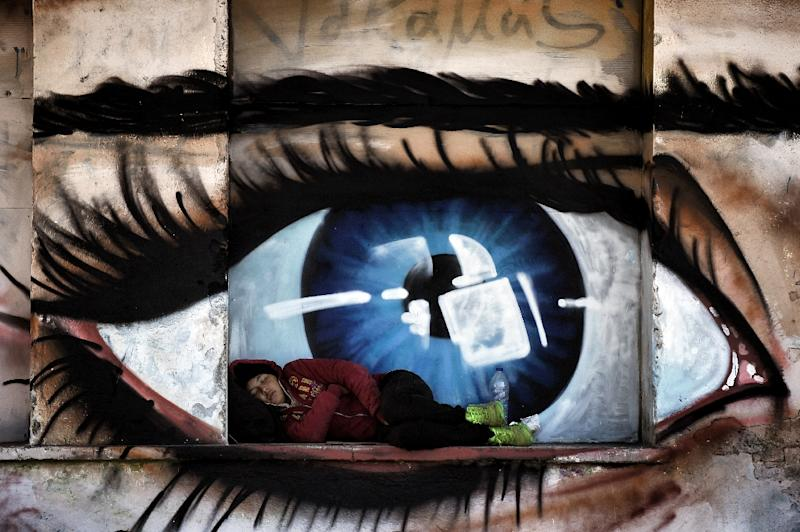 A migrant woman sleeping in front of graffiti at the port of Mytilene on the Greek island of Lesbos, on October 6, 2015 (AFP Photo/Aris Messinis)