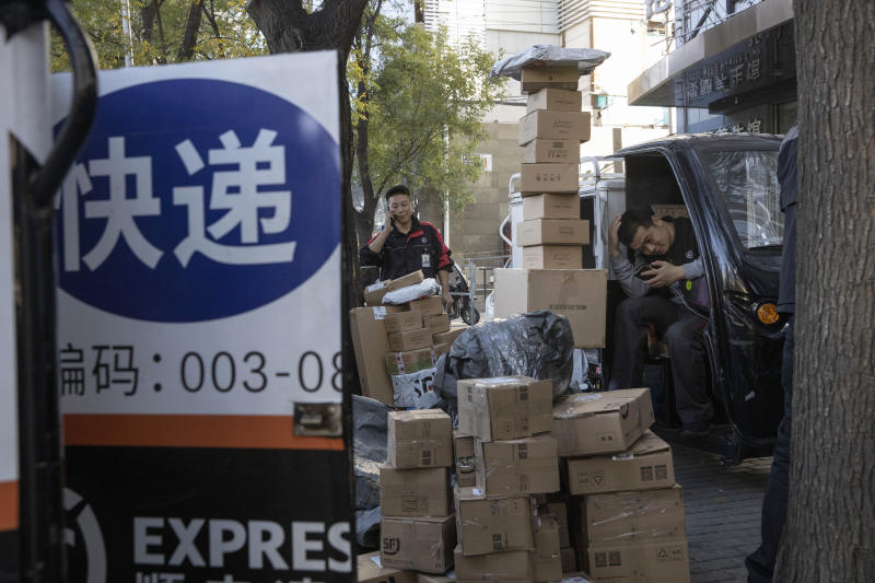 """ADDS TRANSLATION - Delivery men wait to distribute parcels on the streets of Beijing on Monday, Nov. 11, 2019. Chinese e-commerce giants Alibaba and JD.com reported a total of more than $50 billion in sales on Monday in the first half of Singles Day, an annual marketing event that is the world's busiest online shopping day. The sign reads """"Delivery."""" (AP Photo/Ng Han Guan)"""