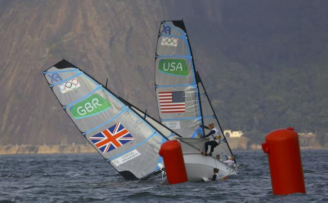 2016 Rio Olympics - Sailing - Final - Women's Skiff - 49er FX - Medal Race - Marina de Gloria - Rio de Janeiro, Brazil - 18/08/2016. Charlotte Dobson (GBR) of Britain and Sophie Ainsworth (GBR) of Britain get capsized past Paris Henken (USA) of USA and Helena Scutt (USA) of USA. REUTERS/Brian Snyder FOR EDITORIAL USE ONLY. NOT FOR SALE FOR MARKETING OR ADVERTISING CAMPAIGNS.