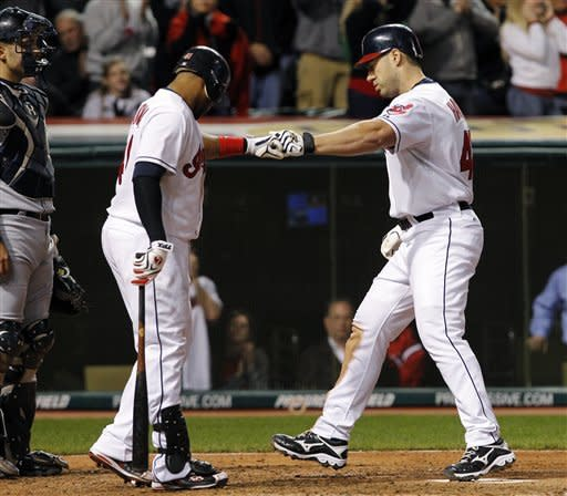 Seattle Mariners catcher Jesus Montero, left, watches Cleveland Indians' Carlos Santana, center, congratulates teammate Travis Hafner after Hafner hit a solo home run during the sixth inning of a baseball game in Cleveland on Wednesday, May 16, 2012. (AP Photo/Amy Sancetta)