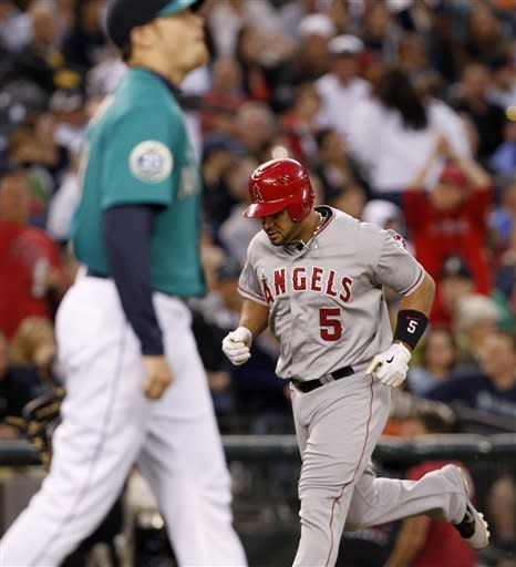 Seattle Mariners starting pitcher Blake Beavan, left, walks back toward the mound as Los Angeles Angels' Albert Pujols circles the bases behind on his three-run home run in the sixth inning in a baseball game Friday, May 25, 2012, in Seattle. (AP Photo/Elaine Thompson)