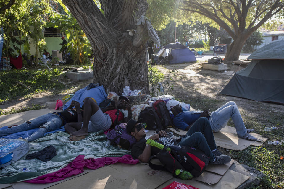 Migrants rest under the shade of a tree in Ciudad Acuna, Mexico, Friday, Sept. 24, 2021, across the Rio Grande from Del Rio, Texas. No migrants remained Friday at the Texas border encampment in Del Rio where almost 15,000 people — most of them Haitians — had converged just days earlier seeking asylum, local and federal officials said. (AP Photo/Felix Marquez)