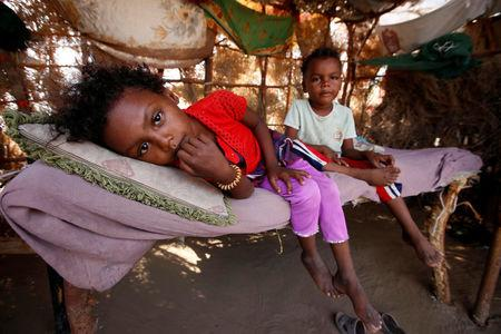 Children rest on a bed at their family hut at a poor neighbourhood on the outskirts of the Red Sea port city of Hodeida