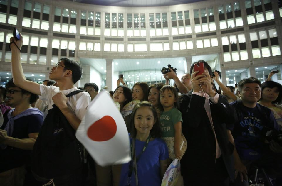 """A girl waves Japan's national flag as visitors take photos during an event titled """"Tokyo 2020 Host City Welcoming Ceremony"""", upon the delegation's return, at the Tokyo Metropolitan Government Building in Tokyo September 10, 2013. Japan savoured its victory on Monday in the race to host the 2020 Olympic Games, anticipating an economic boost to spur its revival from two decades of stagnation and help it recover from the devastating 2011 earthquake and tsunami. REUTERS/Issei Kato (JAPAN - Tags: SPORT OLYMPICS POLITICS)"""