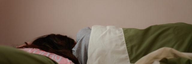 a young woman lying in a bed with face toward the wall