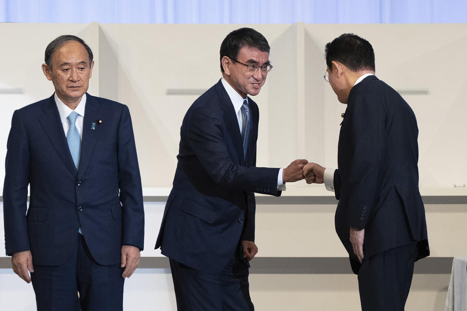 Japan's outgoing Prime Minister Yoshihide Suga, left, pauses while Taro Kono, center, Regulatory Reform and Vaccine minister and a failed leadership candidate, fist bumps with former Foreign Minister Fumio Kishida after Kishida was announced the winner of the Liberal Democrat Party leadership election in Tokyo Wednesday, Sept. 29, 2021. Kishida won the governing party leadership election on Wednesday and is set to become the next prime minister, facing the imminent task of addressing a pandemic-hit economy and ensuring a strong alliance with Washington to counter growing regional security risks. (Carl Court/Pool Photo via AP)