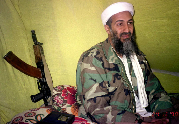 FILE - In this Dec. 24, 1998, file photo, al-Qaida leader Osama Bin Laden speaks to a selected group of reporters in mountains of Helmand province in southern Afghanistan. Years after the death of his father at the hands of a U.S. Navy SEAL raid in Pakistan, Hamza bin Laden himself clearly in the crosshairs of world powers. The U.S. has put up to a $1 million bounty for him. The U.N. Security Council has named him to a global sanctions list, sparking a new Interpol notice for his arrest. His home country of Saudi Arabia has revoked his citizenship. (AP Photo/Rahimullah Yousafzai, File)