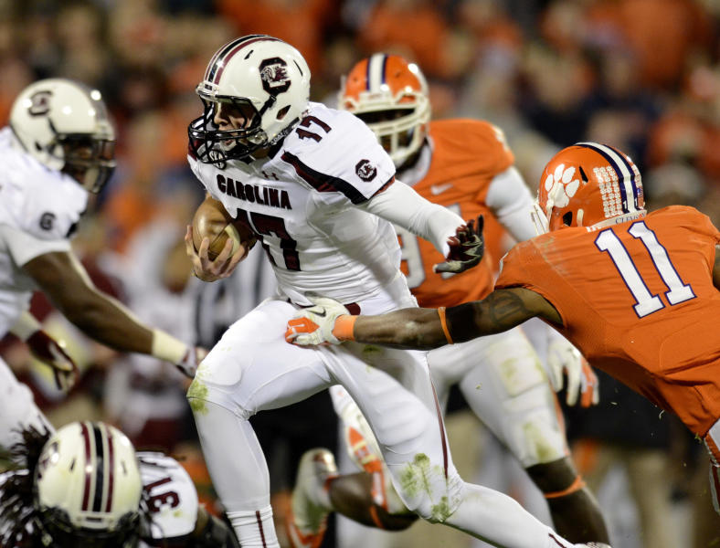 South Carolina quarterback Dylan Thompson, center, scrambles out of the pocket away from Clemson's Travis Blanks (11) during the first half of an NCAA college football game on Saturday, Nov. 24, 2012, at Memorial Stadium in Clemson, S.C. (AP Photo/Richard Shiro)