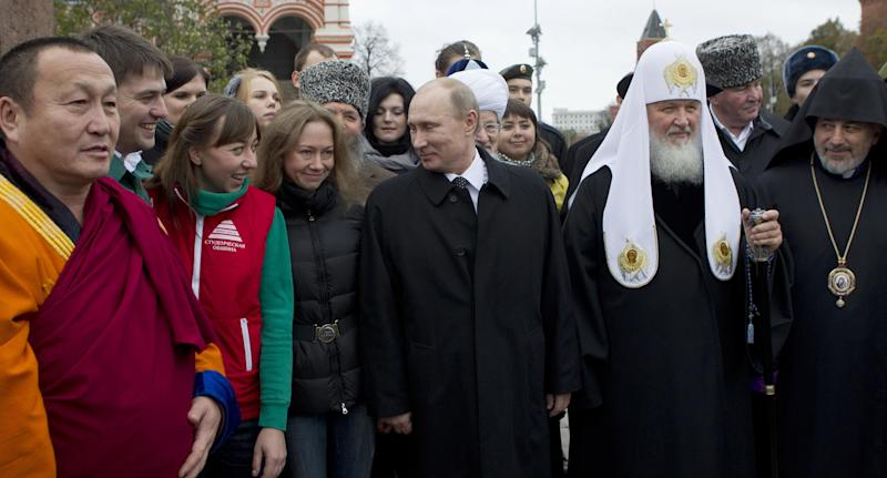 Russian President Vladimir Putin, front centre, speaks with guests and religious leaders of various faiths after a ceremony at the statue of Minin and Pozharsky, the leaders of a struggle against foreign invaders in 1612, to mark the National Unity Day, at the Red Square in Moscow, Sunday, Nov. 4, 2012. The new holiday was created in 2005 to replace the traditional Nov. 7 celebration of the 1917 Bolshevik rise to power. The Kremlin has tried to give it historical significance by tying it to the 1612 expulsion of Polish and Cossack troops who briefly seized Moscow at a time of political disarray. But it has been seized upon by extreme nationalists. (AP Photo/ Misha Japaridze)