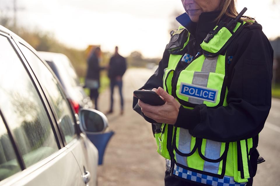 Female Traffic Police Officer Recording Details Of Road Traffic Accident On Mobile Phone